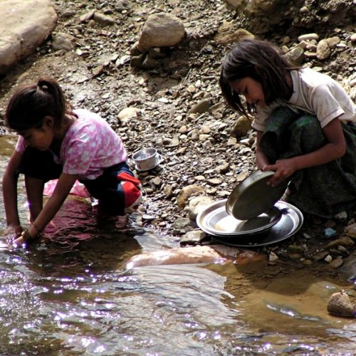 washing dishes in river